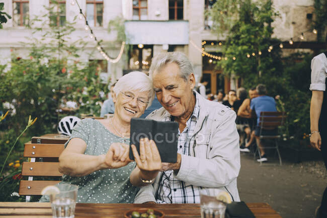 Smiling woman taking selfie with senior man while sitting at restaurant in city — Stock Photo