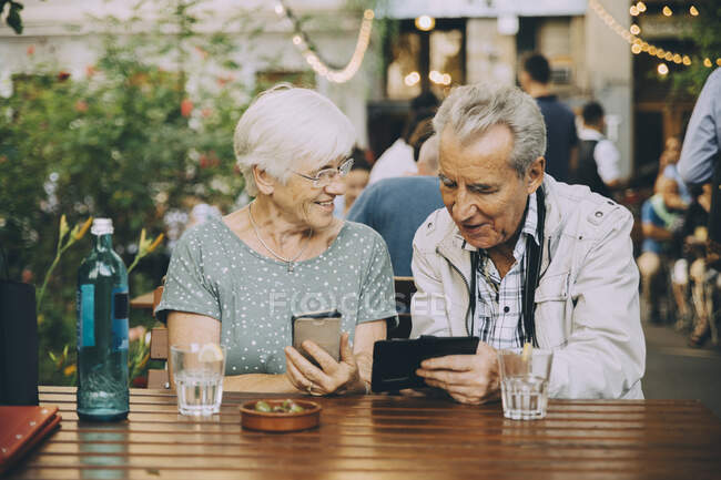 Retired couple using mobile phone while sitting at restaurant in city — Stock Photo