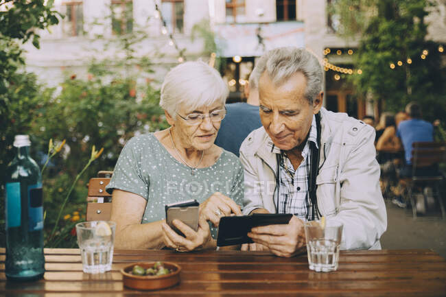 Senior couple using smart phone while sitting at restaurant in city — Stock Photo