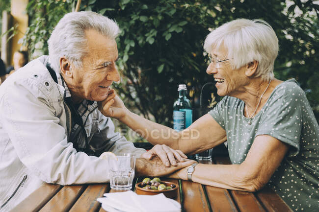 Smiling senior woman touching partner's cheek while sitting at restaurant in city — Stock Photo