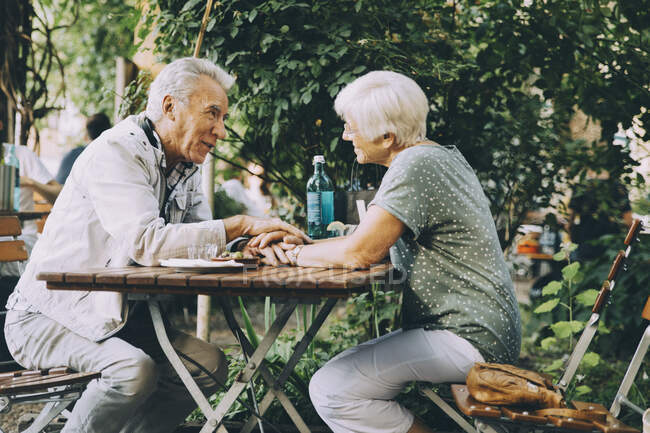 Senior couple holding hands talking while sitting at restaurant in city — Stock Photo