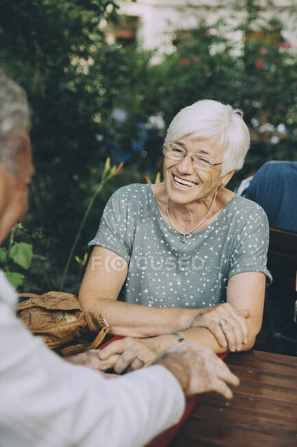 Smiling senior woman looking at partner while sitting at restaurant in city — Stock Photo