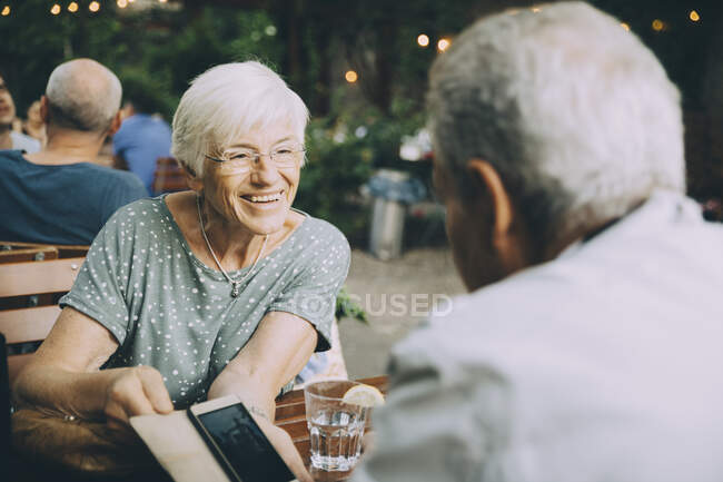 Smiling woman showing mobile phone to senior man while sitting at restaurant in city — Stock Photo