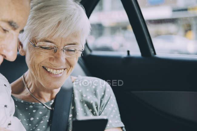 Sorridente donna anziana che mostra il telefono cellulare all'uomo seduto in auto — Foto stock