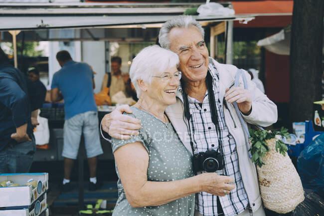 Sorrindo casal sênior com braço em torno de pé no mercado na cidade — Fotografia de Stock