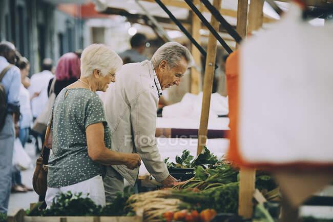 Altos hombres y mujeres que compran hortalizas en el mercado de la ciudad - foto de stock