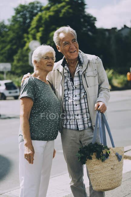 Uomo anziano braccio intorno in piedi con la donna su strada in città — Foto stock