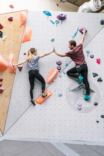 Rear view of male and female friends giving high-five while climbing wall at gym — Stock Photo