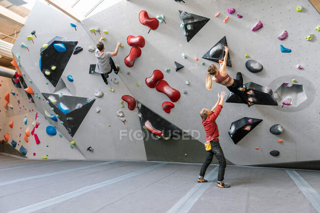 Male trainer training woman and man in wall climbing at gym — Stock Photo