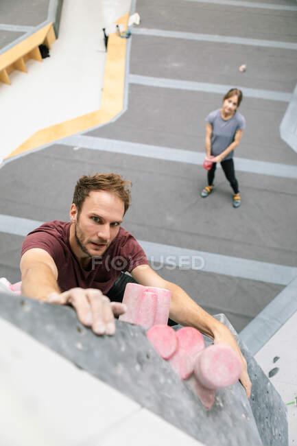 Portrait en grand angle d'un homme pratiquant l'escalade au gymnase — Photo de stock