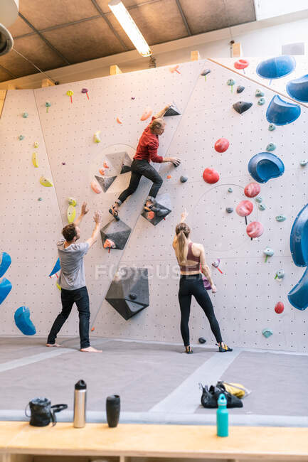 Mature coach showing wall climbing to male and female in gym — Stock Photo