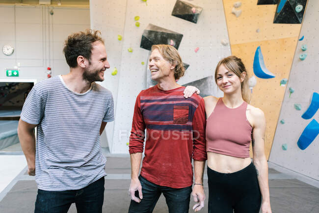 Portrait of smiling female standing with coach and male student in gym — Stock Photo