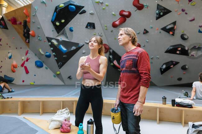 Зрелые инструменты с девушкой-студенткой, смотрящей вверх, стоя в спортзале — стоковое фото