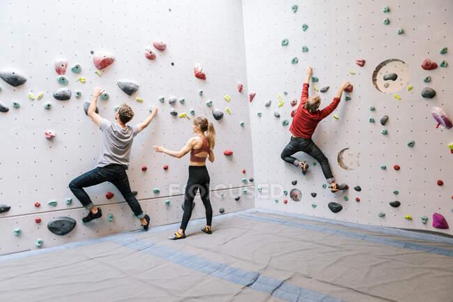 Instrutor de formação de alunos do sexo masculino e feminino rock escalada no ginásio — Fotografia de Stock