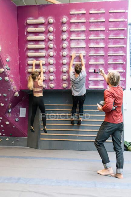 Studenti di sesso maschile e femminile che praticano l'arrampicata a parete mentre allenatore maturo fotografa in palestra — Foto stock