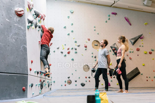 Side view of mature coach training male and female students for wall climbing in gym — Stock Photo