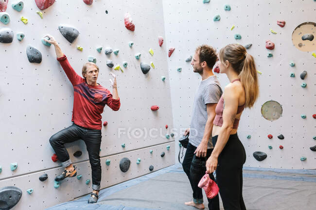 Mature instructor teaching students about bouldering in gym — Stock Photo