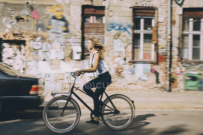 Вид сбоку на молодую предпринимательницу, катающуюся на велосипеде против застройки в городе — стоковое фото