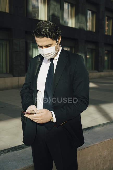 Homme d'affaires avec masque facial utilisant un smartphone — Photo de stock