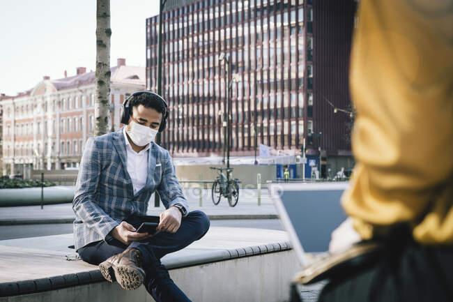 Geschäftsmann mit Gesichtsmaske sitzt mit Smartphone draußen — Stockfoto