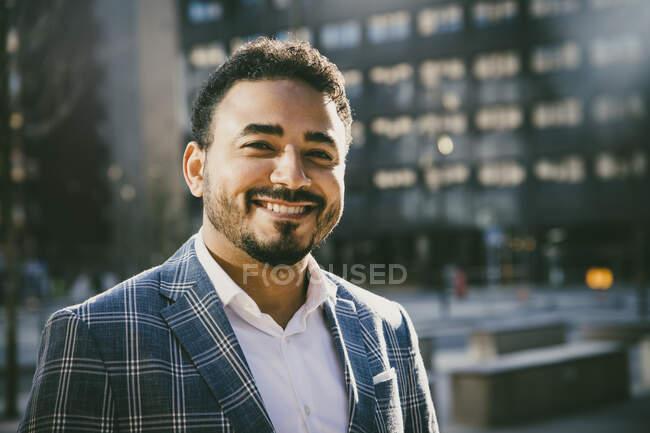 Porträt eines lächelnden Geschäftsmannes vor einem Bürogebäude — Stockfoto