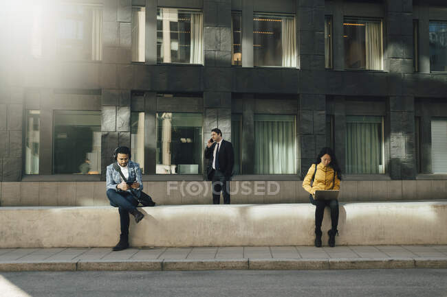 Three people keeping social distancing working outdoors — Stock Photo