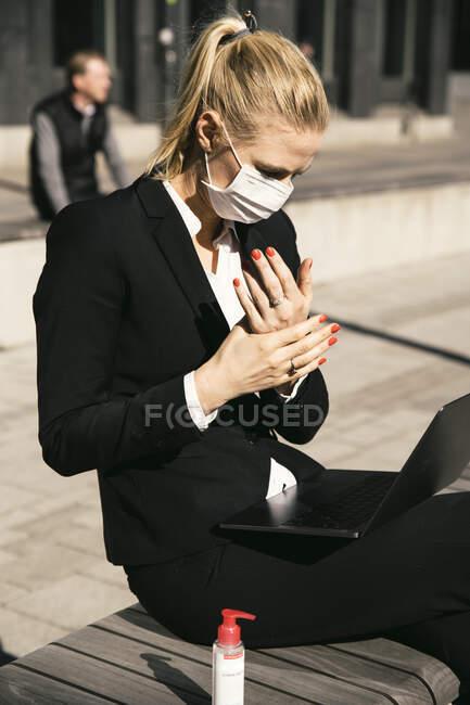 Empresária trabalhando com laptop máscara facial waring e higienizador de mãos — Fotografia de Stock