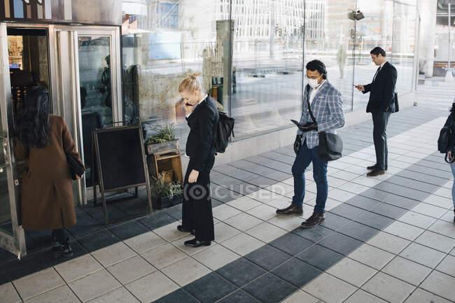Gente de pie en la cola fuera de la cafetería manteniendo distancia - foto de stock