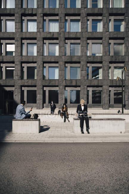 Gli uomini d'affari in piazza mantenendo la distanza sociale — Foto stock