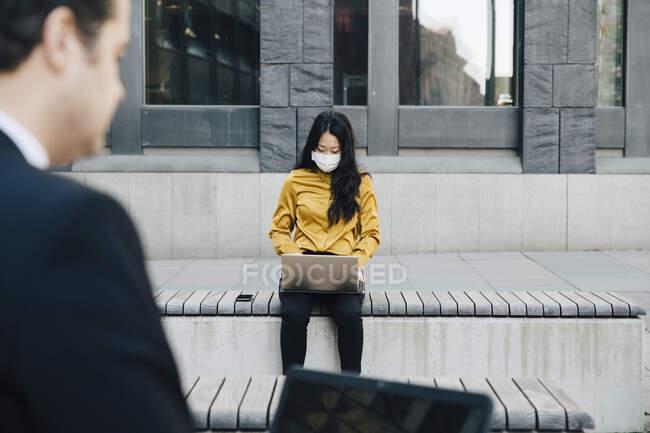 Les hommes d'affaires utilisant un ordinateur portable portant un masque facial — Photo de stock