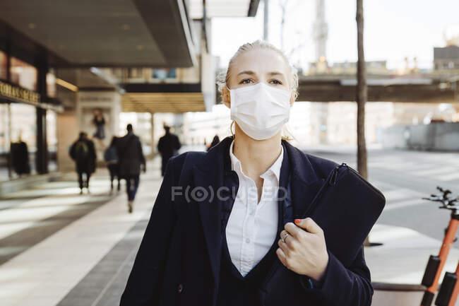 Femme d'affaires marchant dans la rue portant un masque facial — Photo de stock