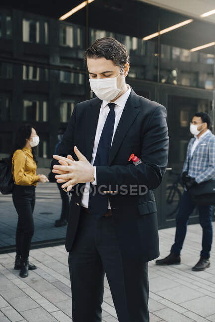 Businessman with face mask washing hands with hand sanitiser — Stock Photo