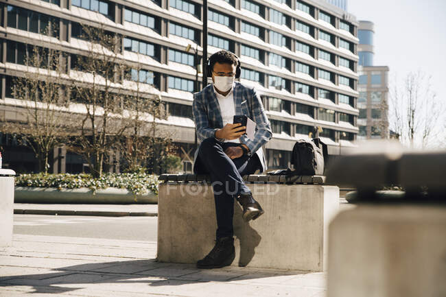 Homme d'affaires avec masque facial à l'aide d'un téléphone mobile — Photo de stock