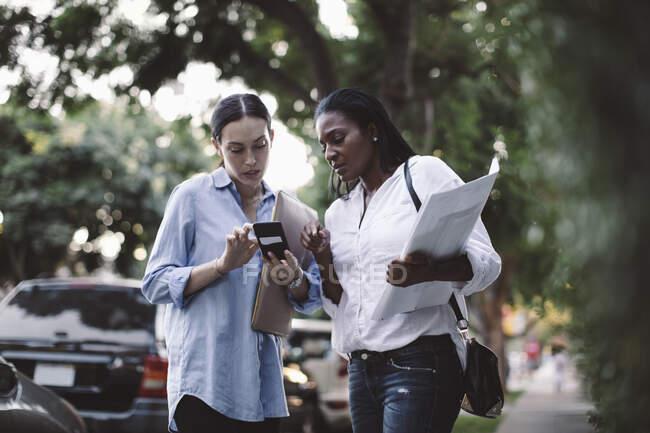 Низький кут зору підприємця, який показує смартфон співробітнику, стоячи на відкритому повітрі. — стокове фото