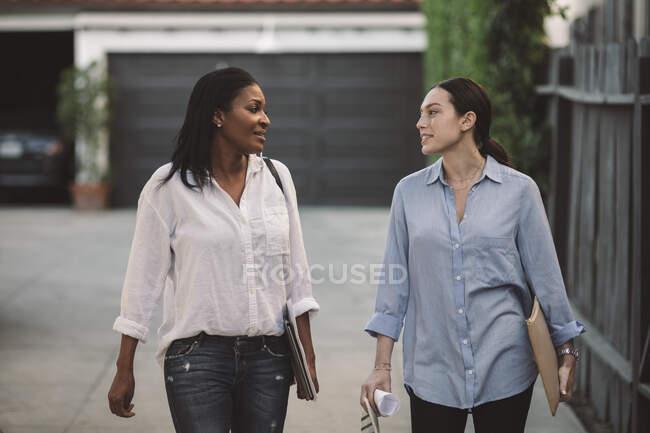 Жіночі архітектори обговорюють під час ходьби по дорозі. — стокове фото