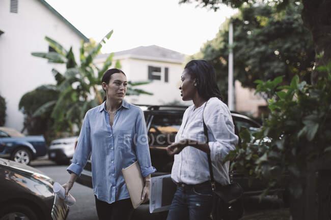 Жіночі дизайнери спілкуються під час ходьби по дорозі проти автомобіля. — стокове фото