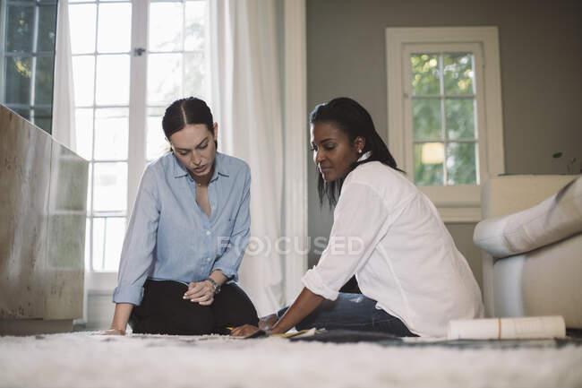 Architectes femmes discutant tout en étant assis sur le tapis au bureau à la maison — Photo de stock