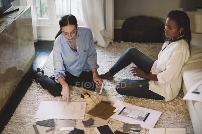 Vue en angle élevé de designers féminins discutant de tissu swatch tout en étant assis sur le tapis au bureau à la maison — Photo de stock