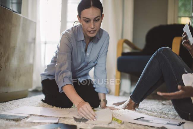 Femme designer discuter de tissu swatch avec collègue tout en s'agenouillant sur le tapis au bureau à la maison — Photo de stock