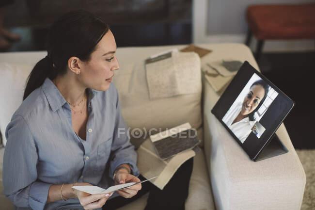 Arquiteto com tela swatch falando através de laptop em videoconferência enquanto trabalhava em casa — Fotografia de Stock