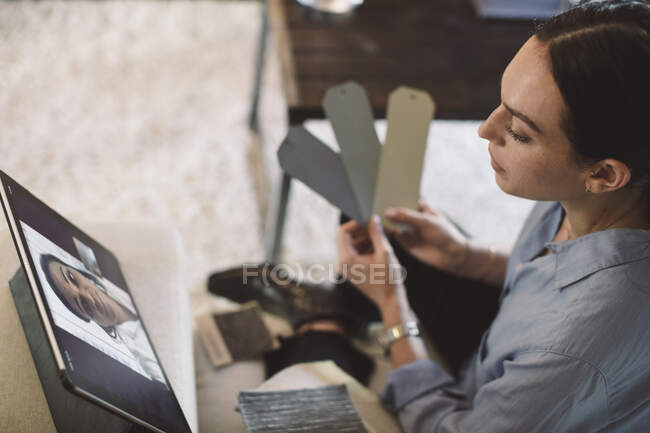 High angle view of female entrepreneur holding labels while talking to colleague on video conference at home office — Stock Photo