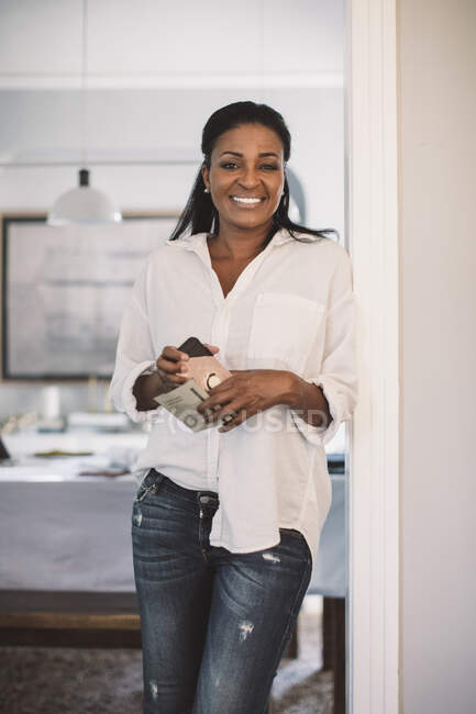 Portrait of smiling female designer with smart phone standing at home office — Stock Photo