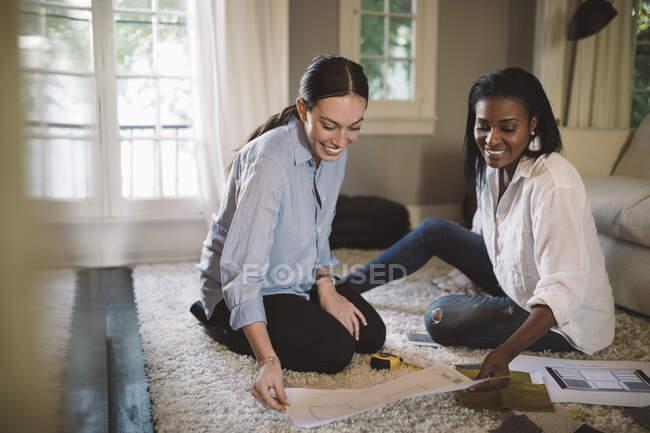 Lächelnde Designerinnen diskutieren auf Teppich im Home Office — Stockfoto