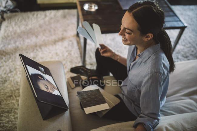 Vista de gran angular de las mujeres empresarias sonrientes que mantienen un intercambio de tejidos mientras hablan con su colega sobre videoconferencia a la hora de la verdad. - foto de stock