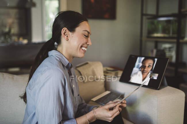 Усміхаючись, жінка - підприємець з тканини говорить через ноутбук на відеоконференції, працюючи вдома. — стокове фото