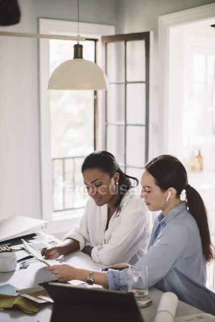 Сторона зору архітектора обговорюється з колегою під час роботи за столом у домашньому офісі. — стокове фото