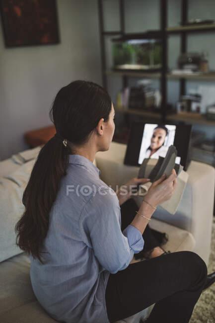 Vista lateral do arquiteto com tela swatch em vídeo conferência através de laptop enquanto trabalhava em casa — Fotografia de Stock