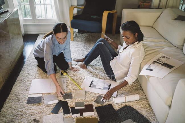 Blickwinkel von Designerinnen, die über Stoffmuster diskutieren, während sie im Home Office auf Teppich sitzen — Stockfoto