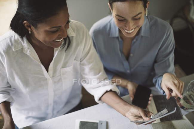 Високий кут зору усміхнених архітекторів обговорюють під час роботи за столом у домашньому офісі. — стокове фото