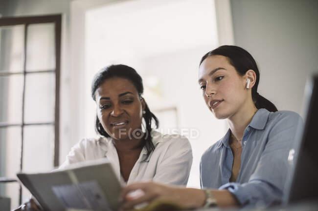 Vue en angle bas des architectes discutant tout en travaillant à table dans le bureau à domicile — Photo de stock